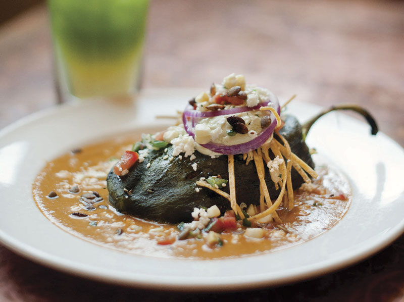 Elote Café's Relleno de Pollo, a fire-roasted poblano chile stuffed with smoked chicken, vegetables and Tillamook cheddar, and topped with pipian rojo