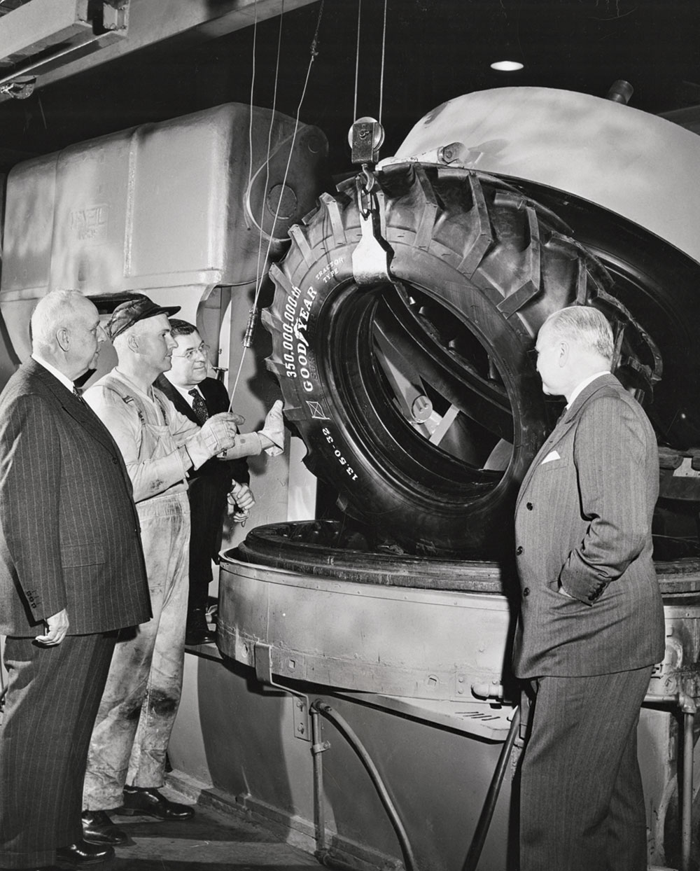 RUBBER MEN: Goodyear Tire and Rubber Co. officials, including board chairman Paul Litchfield (far left) watch the 350,000,000th tire taken from the vulcanizer in the company tire room, 1943.