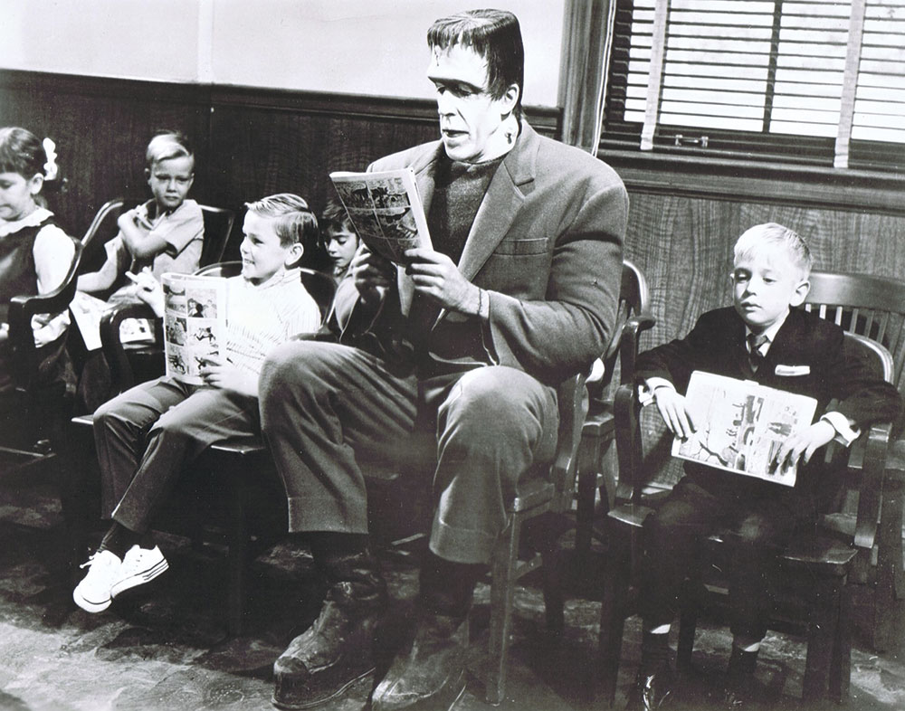 Photo courtesy Michael F. Blake; Then-child actor Michael F. Blake (left) sits next to Fred Gwynne (Herman Munster) while filming The Munsters in 1965. Blake worked as a makeup artist on a Munsters reunion show 15 years later.