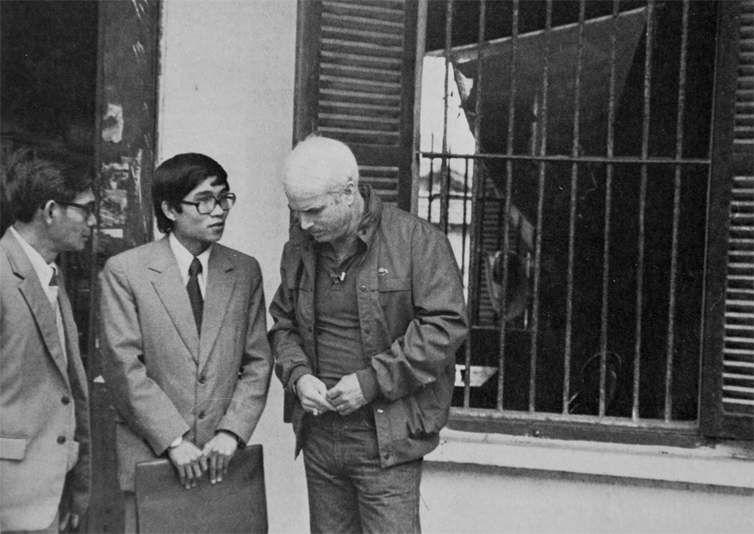 """with Vietnamese officials outside his cell at """"The Plantation,"""" the former POW camp where he spent several years"""