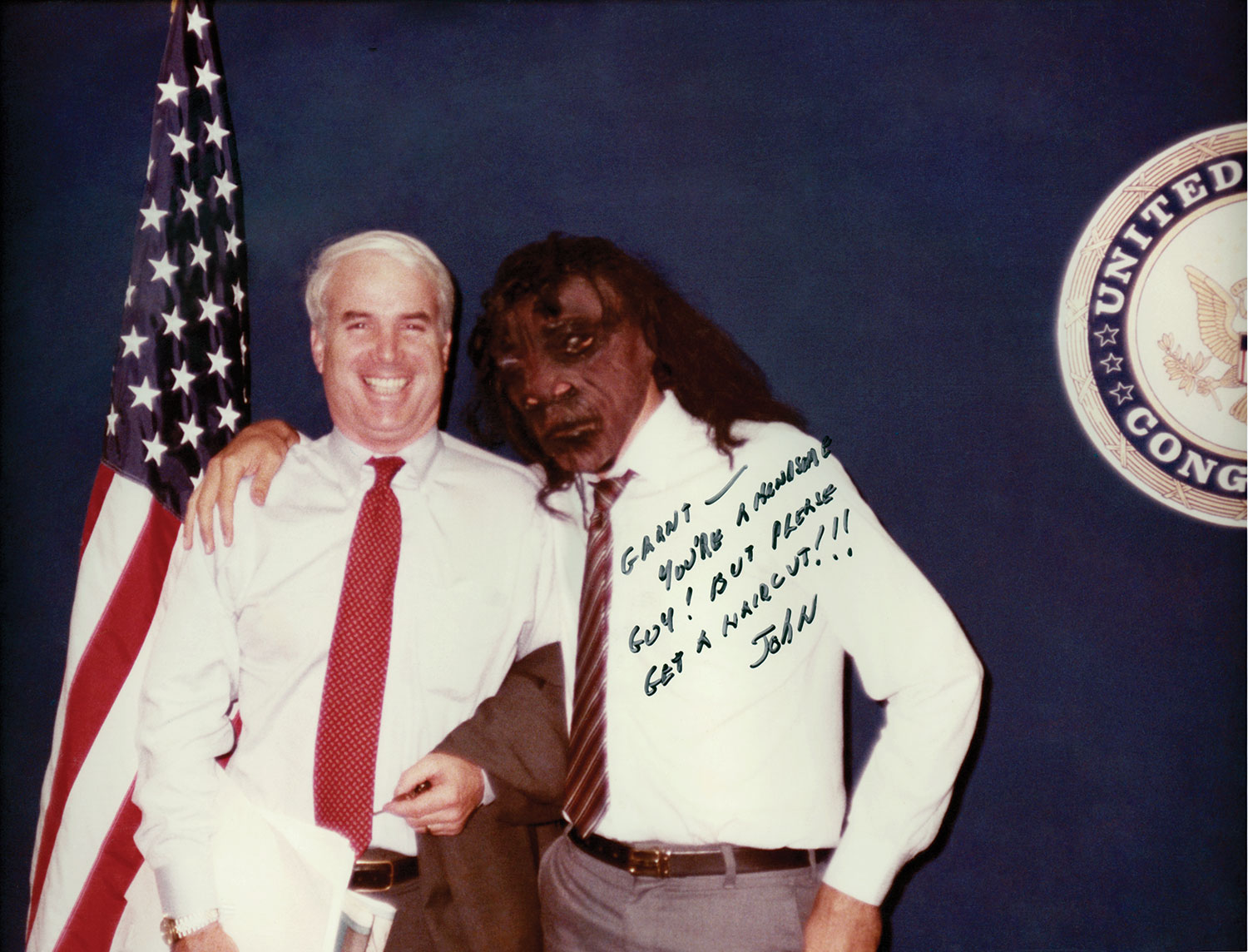 """Posing with Grant Woods, dressed as a caveman, McCain wrote, """"You're a handsome guy! But please get a haircut,"""" circa 1984"""