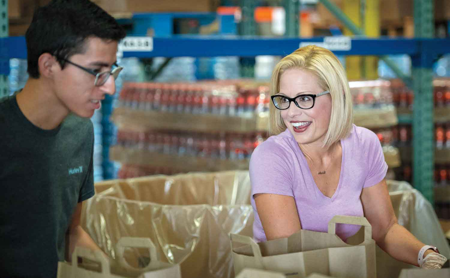 Sinema with a volunteer at a service project at St. Mary's Food Bank in August; Courtesy Sinema Campaign