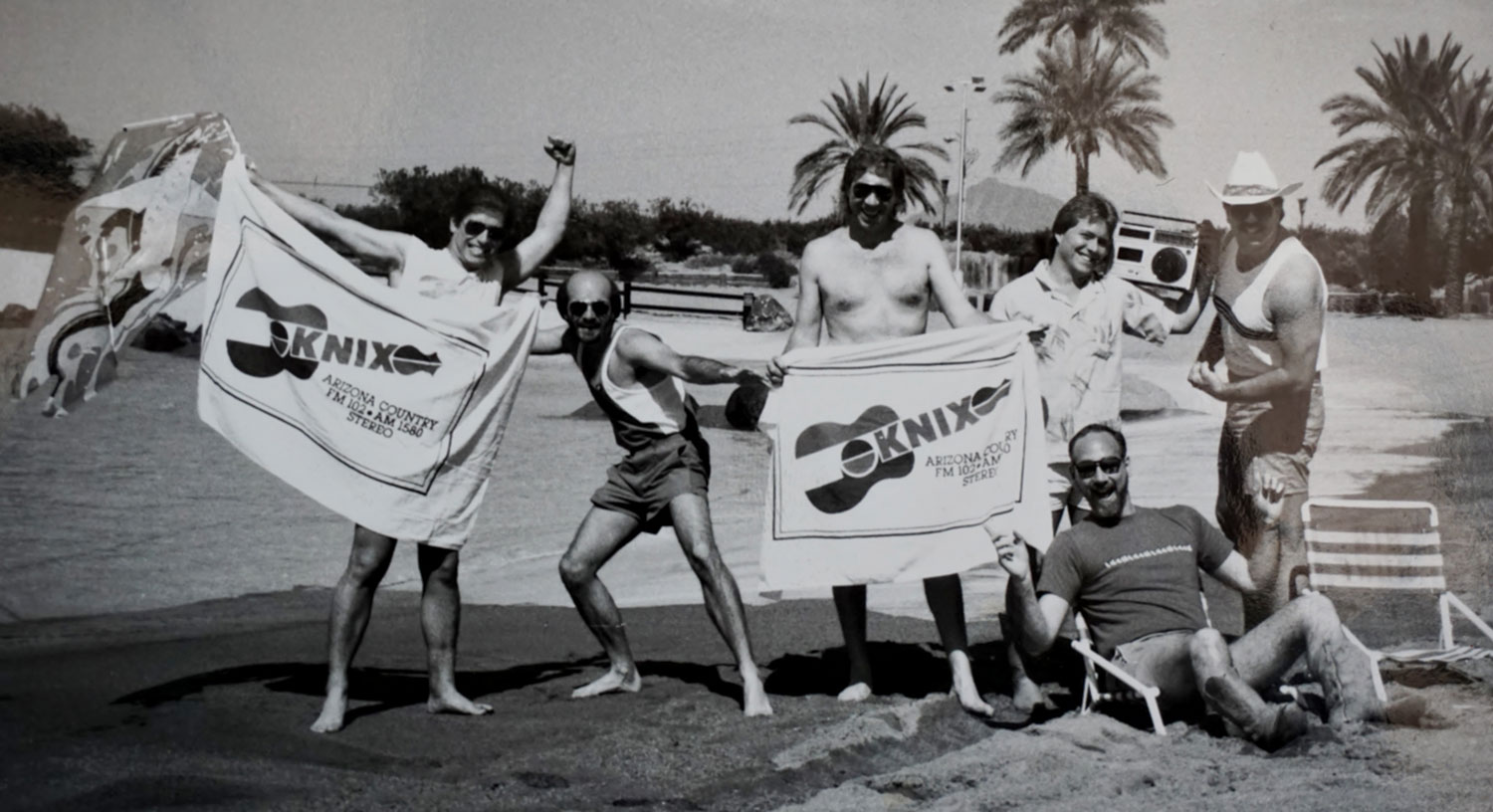 : KNIX talent (including station co-owner Buddy Owens, third from left) catch some rays, 1988