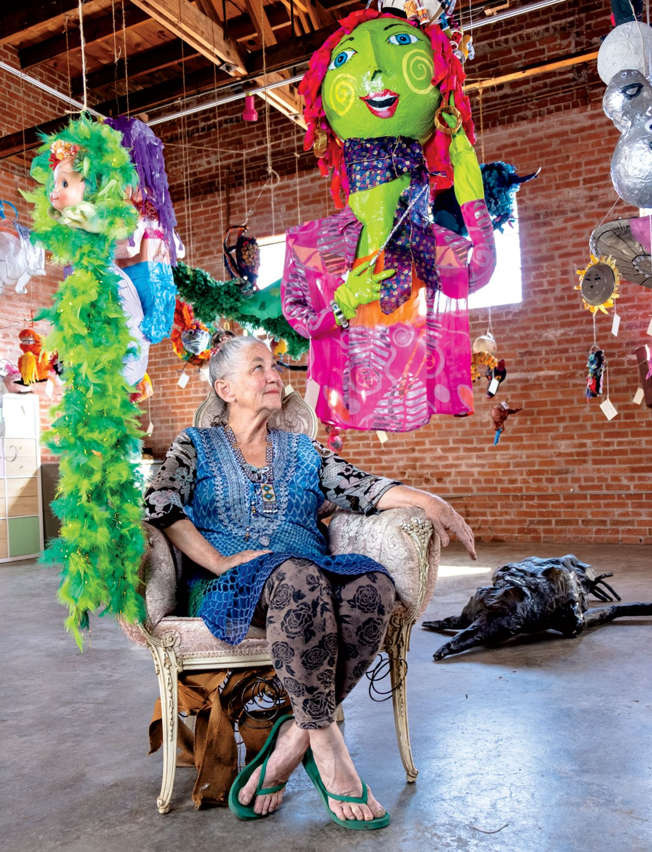 Photo by Mirelle Inglefield; Beatrice Moore in her Weird Garden gallery, flanked by piñatas during the 2019 Art Detour.