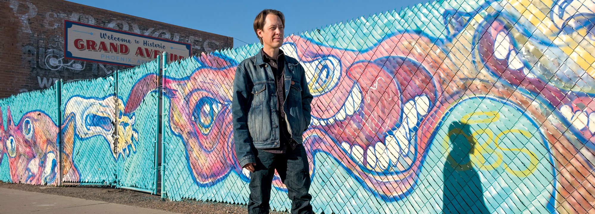 "David Quan, aka Luster Kaboom, with his ""Fruit Stripes"" mural near 15th and Grand avenues; Photo by Mirelle Inglefield"