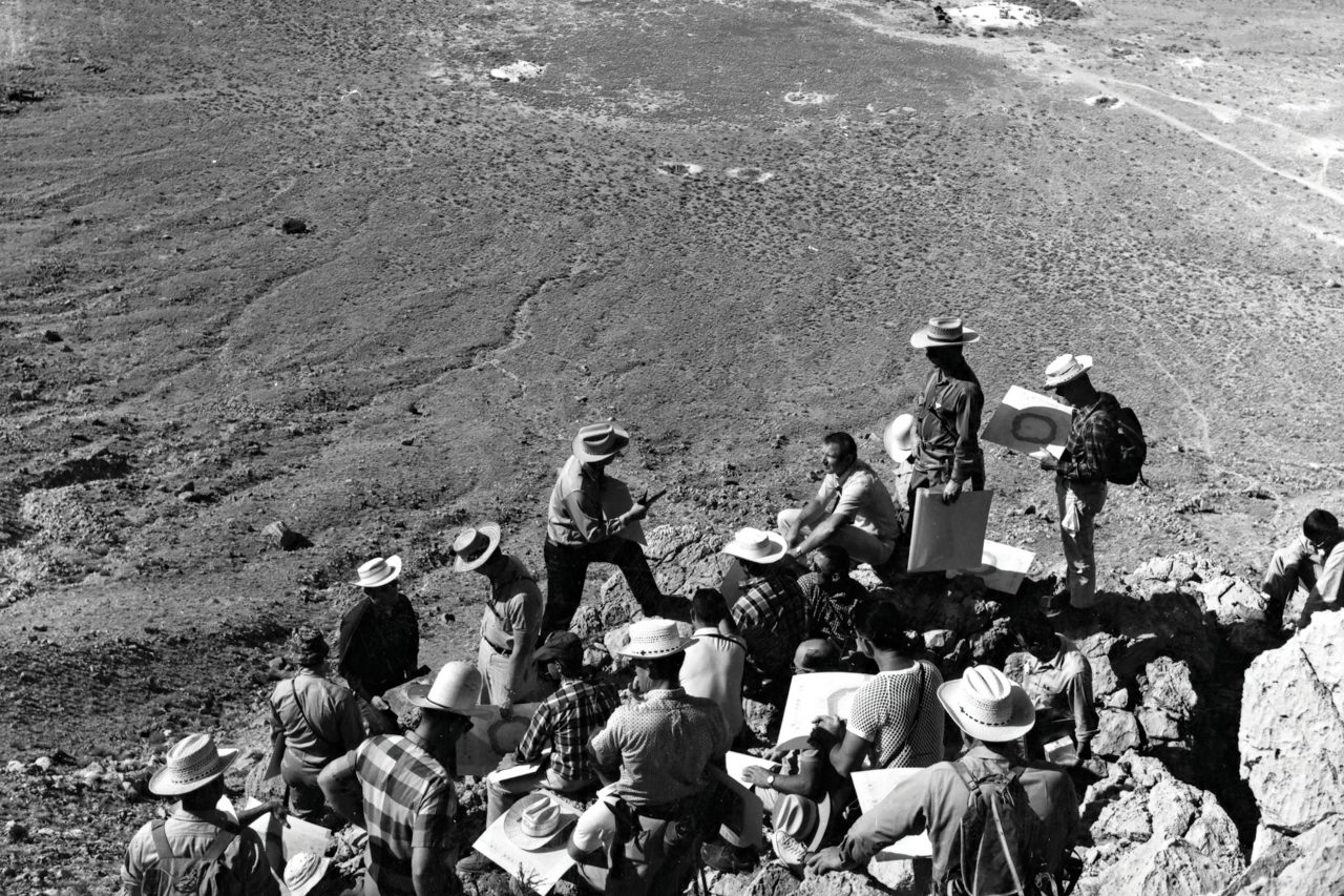Flagstaff geologist Gene Shoemaker describes the lunar geology of Meteor Crater to a large group of Apollo astronauts during a training field trip, May 1967.; Photo courtesy Center of Astrogeology, U.S. Geological Survey, courtesy Cline Library/NAU