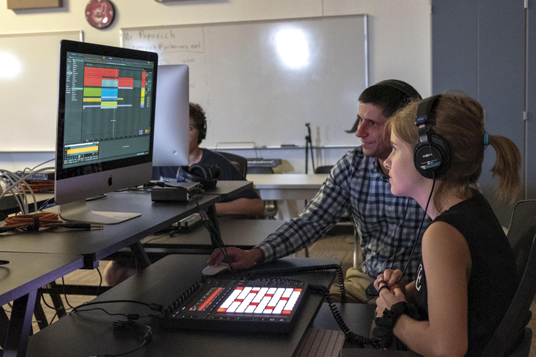Academies music teacher Nick Popovich instructs eighth grader Skylar Pirkey on Ableton Live software.