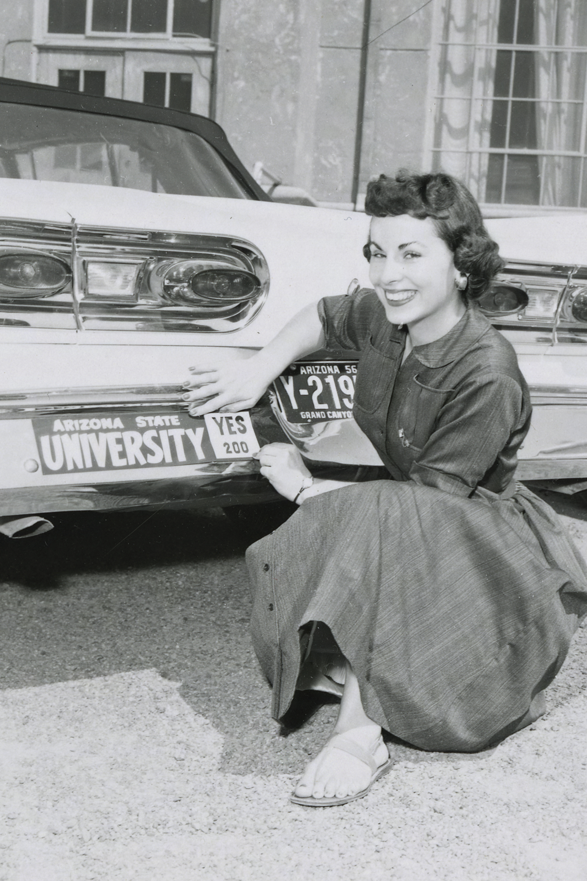 A supporter shows off her Prop. 200 bumper sticker, 1958