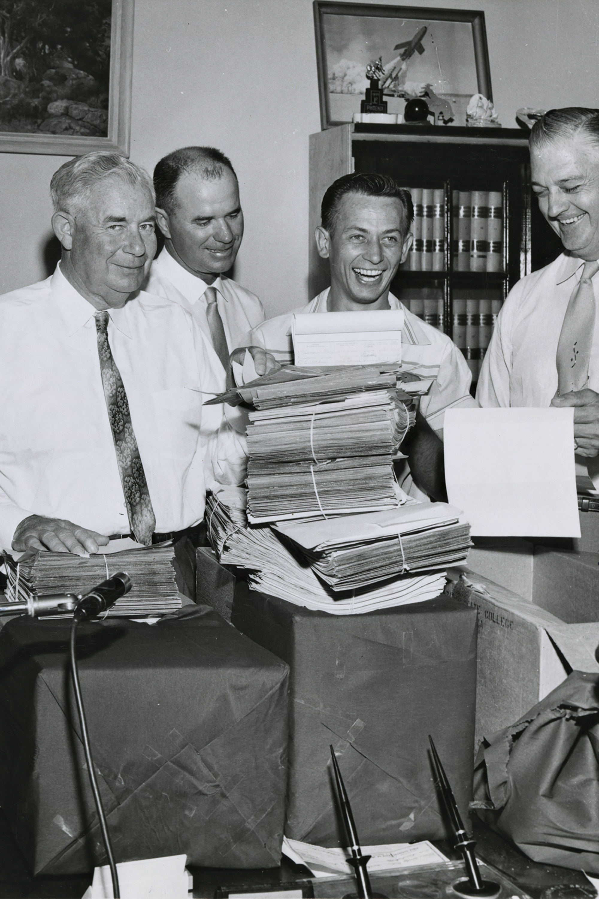 "Gov. Ernest McFarland (far left), an unidentified man, James ""Mr. ASU"" Creasman and Arizona Secretary of State Wesley Bolin celebrate the proposition's passage"