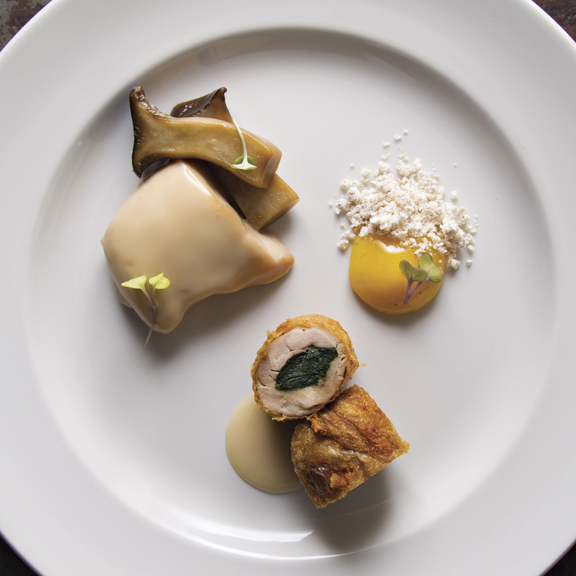 poached Jidori chicken breast and thigh roulade with braised king trumpet mushrooms and 151-degree egg yolk