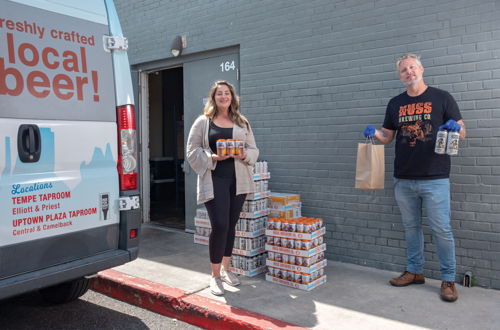 Leah Huss and general manager Mike Chapman fulfill an order for their newly implemented Huss Brewing Co. curbside service.; Photography by Mirelle Inglefield