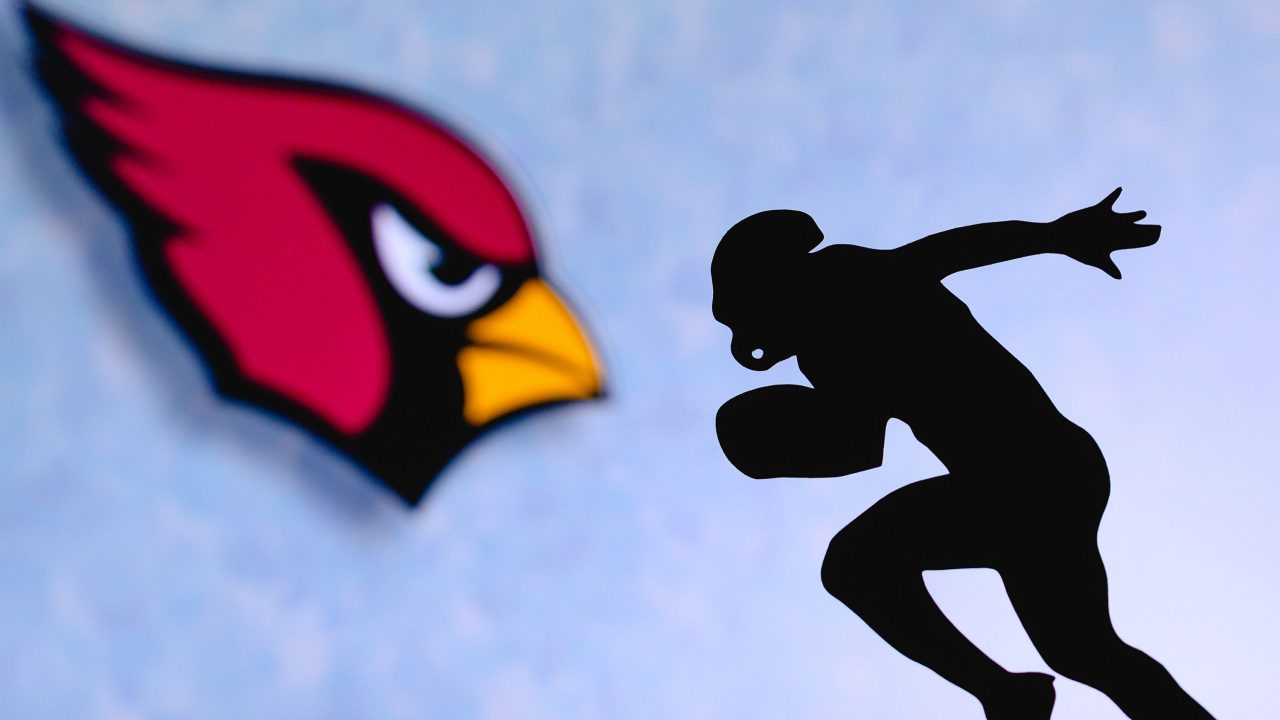 https://www.phoenixmag.com/wp-content/uploads/2021/07/Arizona-Cardinals.-Silhouette-of-professional-american-football-player.-Logo-of-NFL-club-in-background-edit-space.-1280x720.jpg
