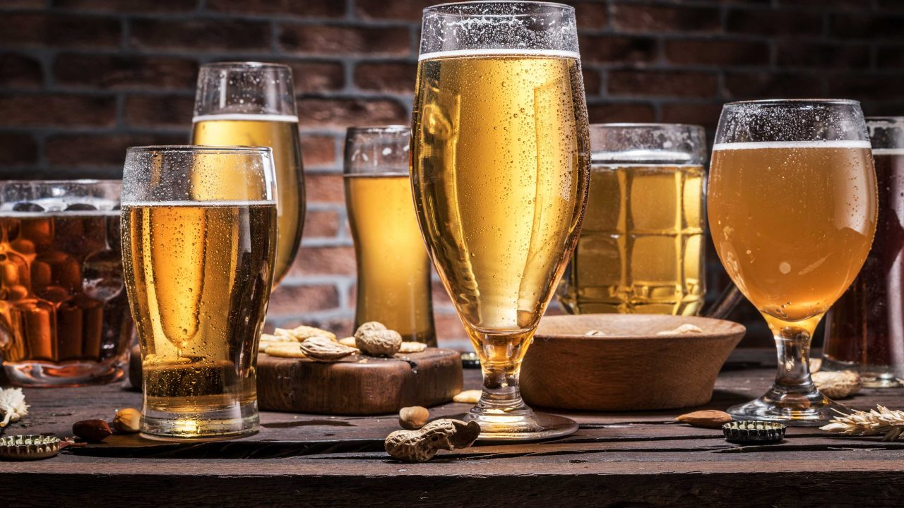 https://www.phoenixmag.com/wp-content/uploads/2021/10/Cold-mugs-and-glasses-of-beer-on-the-old-wooden-table-brick-wall-at-the-background.-Assortment-of-beer.-1280x720.jpg